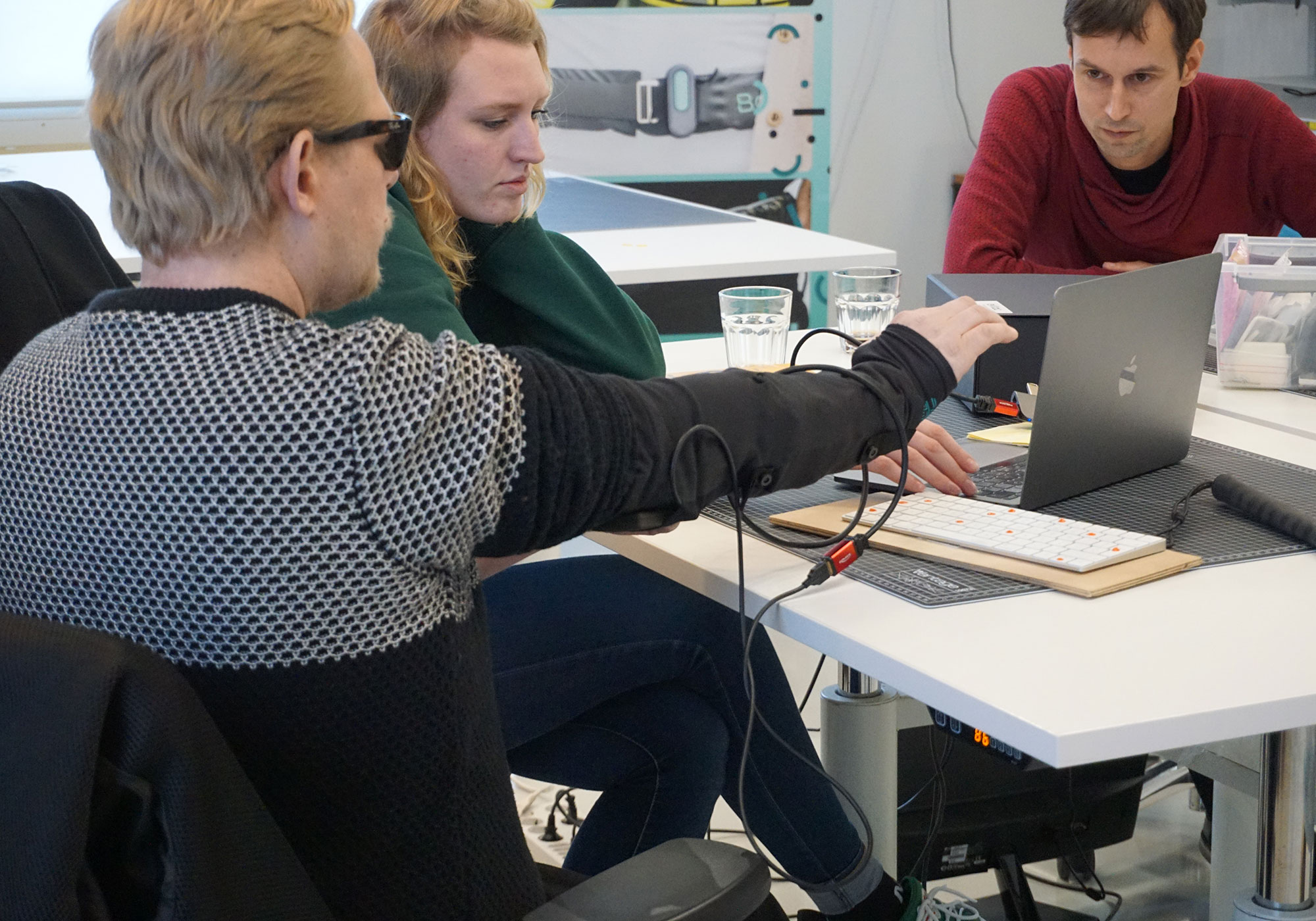 Young man testing a haptic feedback sleeve, with a woman and a man watching intently
