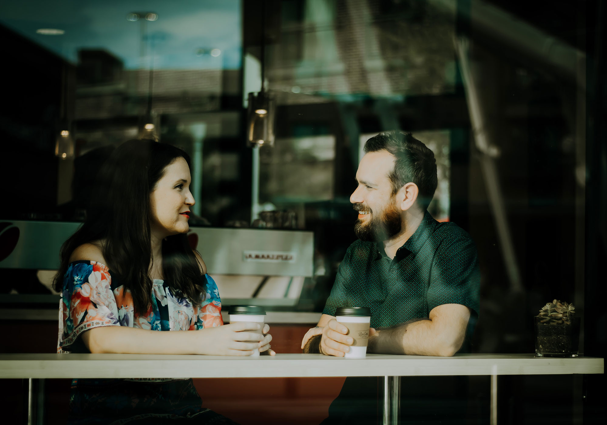 A woman and a man in a coffee house, looking at each other.